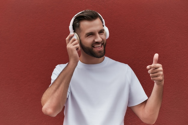 I like this song portrait of happy handsome man in headphones listening to the music