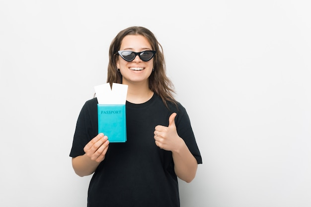 旅行が好きです。若い笑顔の女性は、2つのチケットと親指を立ててパスポートを保持しています。