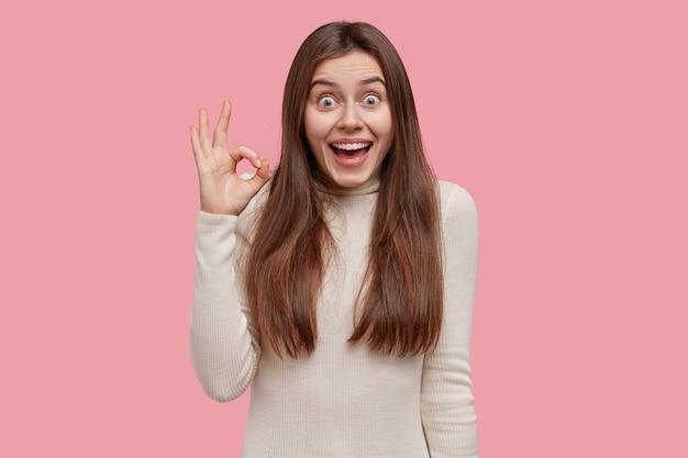 私はすべてが完璧なときに好きです。喜んでいるヨーロッパの女性は、白いタートルネックのセーターを着て、大丈夫なジェスチャーを示し、広く笑顔を見せます