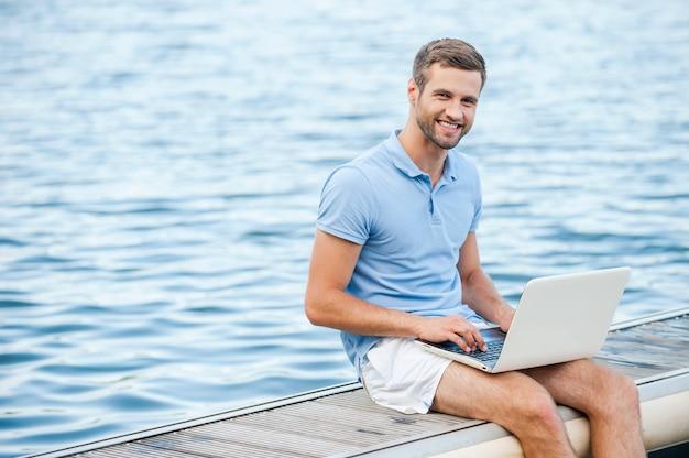 Мне нравится работать на природе! красивый молодой человек в рубашке поло работает на ноутбуке и улыбается, сидя на набережной