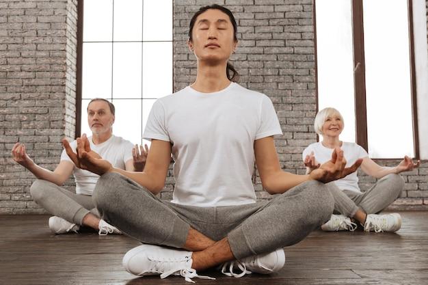 私はヨガが好きです。瞑想しようとしている間彼女の家庭教師の後ろに座っている彼女の顔に笑顔を保つ幸せな年金受給者の女性