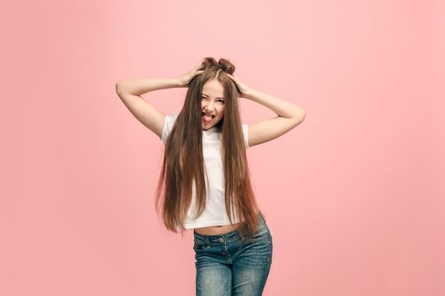 気が散ってました。変な表情の十代の少女。ピンクのスタジオの背景に分離された美しい女性のハーフレングスの肖像画。クレイジーなティーンエイジャー。人間の感情、表情のコンセプト。
