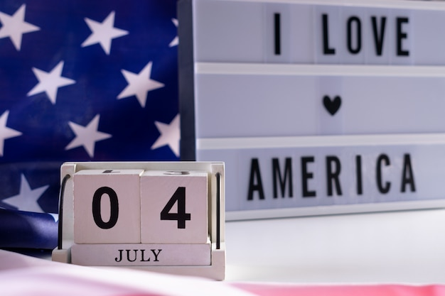 I love america written in light box on usa flag background. happy independence day usa.
