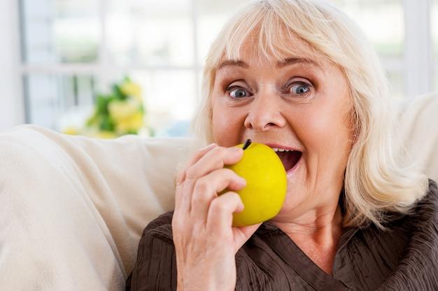 나는 사과를 좋아한다! 사과를 들고 의자에 앉아 카메라를 바라보는 쾌활한 시니어 여성