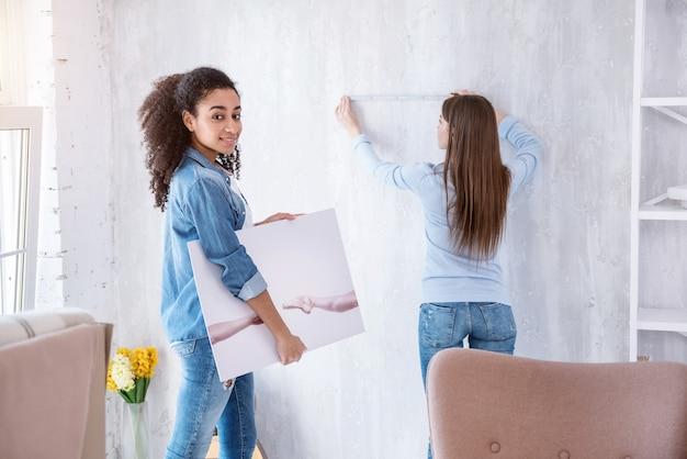 私は芸術が好き。カメラに向かってポーズをとり、ルームメイトが壁を測定して壁を吊るしている間、写真を持っている美しい縮れ毛の少女
