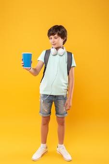 コーヒーが好き。笑顔とアロマコーヒーのカップを保持している陽気な黒髪の少年