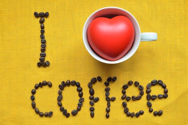 黄色いテーブルクロスの表面に生のコーヒー豆で作られたコーヒーのコンセプトフレーズが大好きです