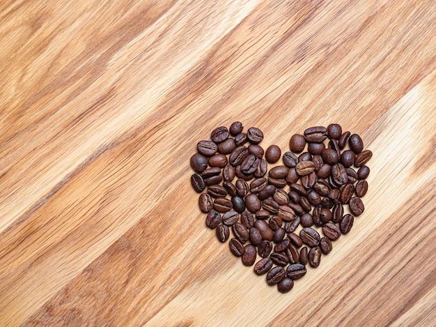 コーヒーが好き。木製のテーブルにハートの形で香りのよいローストコーヒー豆
