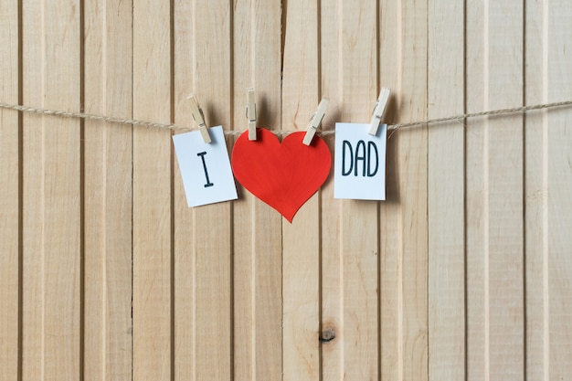 I love dad. fathers day concept. message with paper heart hanging with pins over light wooden board.