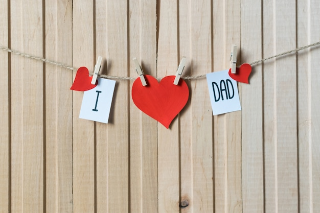 I love dad. fathers day concept. message with paper hearts hanging with pins over light wooden board.