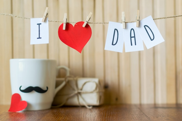I love dad. fathers day greeting. message with paper heart hanging with clothespins over wooden board.