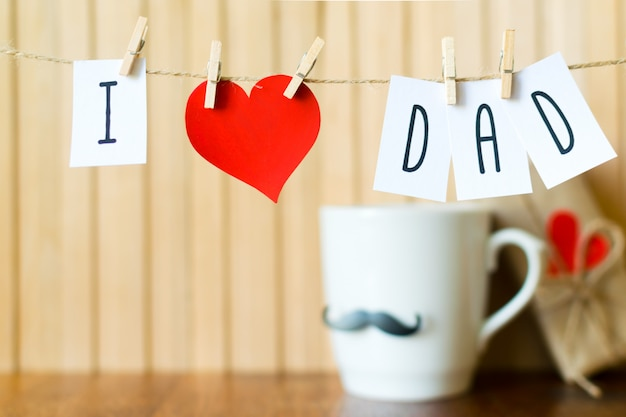 I love dad. fathers day message with paper heart hanging with clothespins over wooden board.