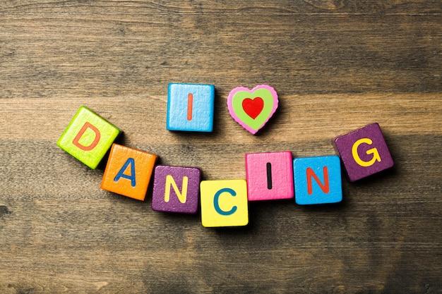 나는 나무 탁자에서 춤추는 레터링 큐브를 좋아한다