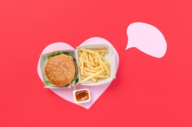 나는 패스트푸드를 좋아한다. 빨간색 배경에 고립 된 심장의 형태로 감자 튀김