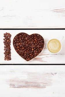 I love fresh cappuccino with foam. roasted coffee seeds arranged in a shape of heart. white wood surface.