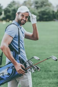 나는 골프를 사랑한다! 드라이버와 골프 가방을 들고 골프 코스에 서있는 동안 어깨 너머로 보는 젊은 행복한 골퍼의 후면보기