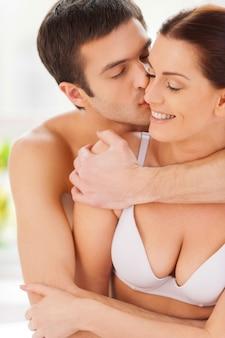 彼女が大好き!男が彼のガールフレンドにキスし、彼女を抱きしめている間、ベッドで一緒に座っている美しい若い愛情のあるカップル
