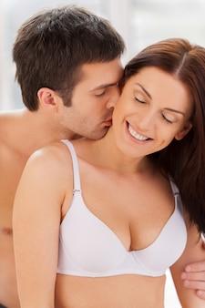 私は彼がそれをするのが大好きです!男が首で彼のガールフレンドにキスしながらベッドで一緒に座っている美しい若い愛情のあるカップル
