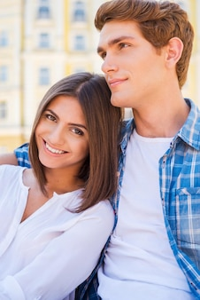 Я люблю его очень сильно! красивая молодая влюбленная пара, сидя на скамейке вместе, пока женщина смотрит в камеру и улыбается