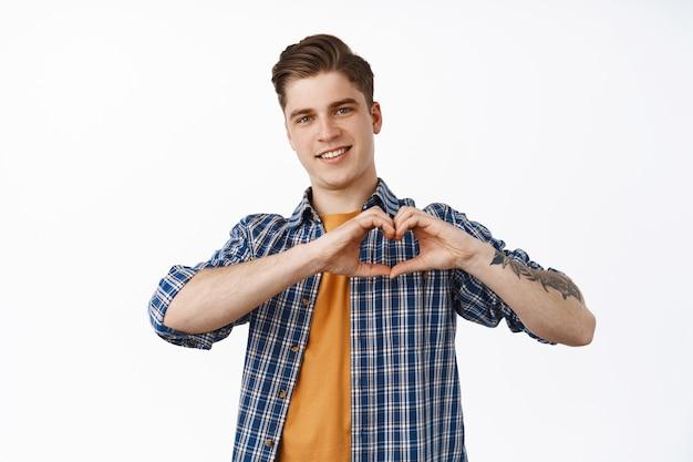 Lo adoro. il giovane ragazzo sorridente e attraente mostra il segno del cuore, si prende cura o come qualcosa, sembra premuroso e adorabile alla macchina fotografica, in piedi in abito casual su bianco