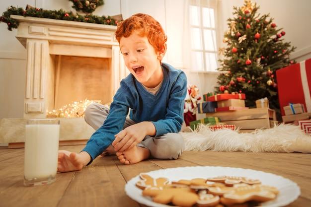 Я очень люблю это. снимок под низким углом эмоционального рыжего ребенка, сидящего на полу за стаканом вкусного молока дома.