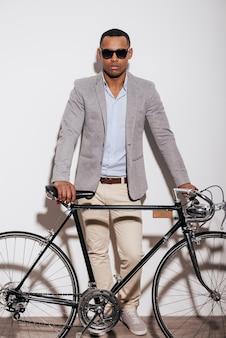 나는 내 자전거를 사랑한다! 그의 복고풍 스타일의 자전거 근처에 서 있는 자신감이 젊은 아프리카 남자의 전체 길이
