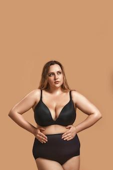 Я люблю свое тело плюс размер молодая женщина в сексуальном черном белье, касаясь ее живота и позирует в студии на коричневом фоне. студийный портрет. женщина с избыточным весом
