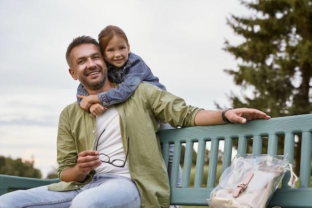 나는 공원에 있는 나무 벤치에 앉아 있는 행복한 아버지와 어린 딸의 아버지 초상화를 사랑합니다