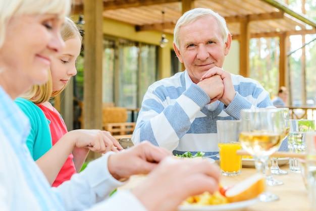 私は家族を愛しています!カメラを見て、家族と一緒に夕食を楽しみながら笑顔の幸せな年配の男性