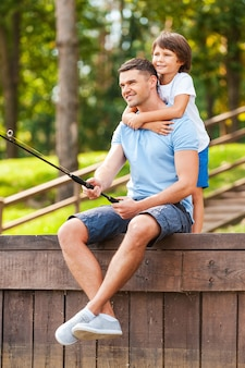 Я люблю своего отца! счастливый отец и сын вместе ловят рыбу на набережной