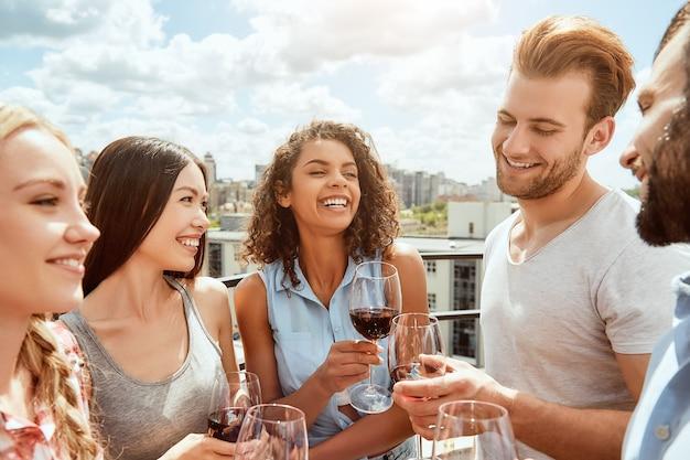 私は幸せな若者の私の友人グループがワインとグラスをチリンと鳴らしているのが大好きです