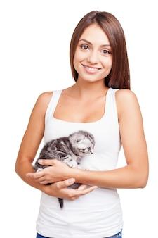 Я люблю своего пушистого маленького друга. красивая молодая женщина, держащая маленького котенка в руках и смотрящая в камеру с улыбкой, стоя изолированной на белом фоне