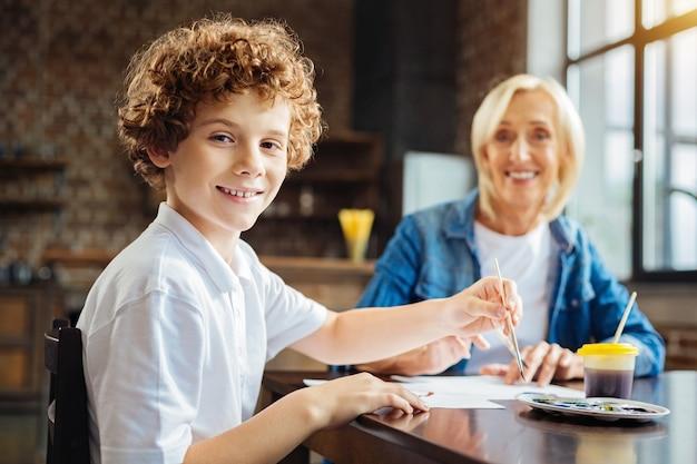 私は祖母が大好きです。テーブルに座って絵を描いている間、彼の顔に陽気な笑顔でカメラを見ている栗の髪の少年に選択的な焦点