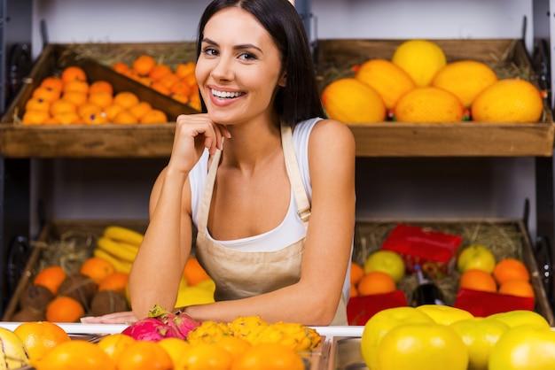 私の仕事が大好きです!あごに手をつないで、背景にさまざまな果物と食料品店に立って笑っているエプロンの美しい若い女性