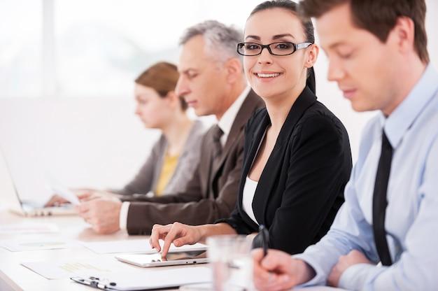 Я люблю свою работу! вид сбоку уверенных деловых людей, сидящих в ряд за столом, в то время как привлекательная женщина смотрит в камеру и улыбается