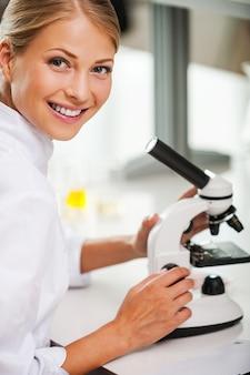 나는 내 일을 사랑한다! 그녀의 작업장에 앉아 있는 동안 현미경을 사용하고 카메라를 보는 쾌활한 젊은 여성 과학자의 상위 뷰