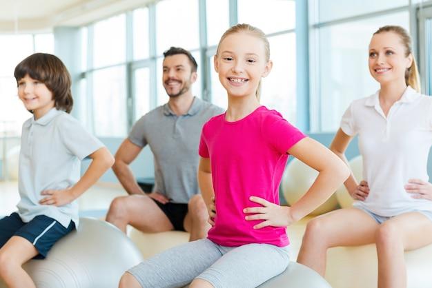 나는 스포츠 가족을 사랑합니다! 스포츠 클럽에서 가족과 함께 운동하는 동안 카메라를 보고 웃고 있는 행복한 어린 소녀