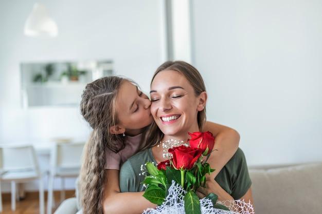 私はあなたのお母さんが大好きです!かわいい女の子と一緒に魅力的な若い女性は、愛のシンボルと花の手作りカードに感謝して、家で一緒に時間を過ごしています。幸せな家族の概念。母の日。