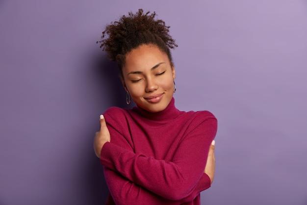 나는 나 자신을 사랑합니다. 부드러운 낭만적 인 여성이 자신의 몸을 감싸고, 자신을 껴안고, 쾌락에서 눈을 감고, 추운 날씨를 위해 부드러운 터틀넥을 입고, 편안함을 느끼고, 보라색 벽에 실내에 서 있습니다.
