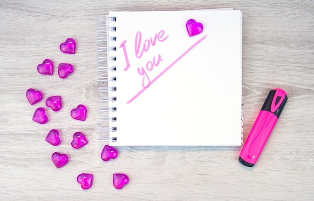 I love a pink letter, a valentine card, a notepad with the words i love you and a pen lying on a white background. valentine day. love letter. marker writing