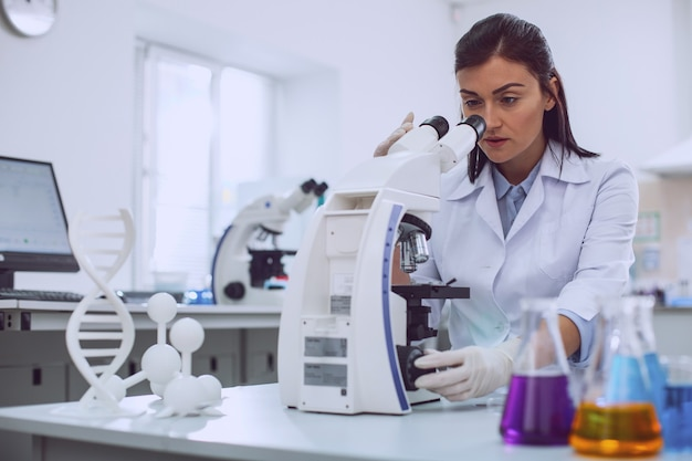 I love science. concentrated professional biologist wearing a uniform and looking into the microscope