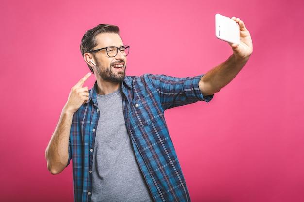 自撮り大好き!カメラを保持しているとselfieを作ると笑顔のシャツでハンサムな若い男