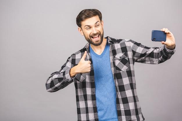 自撮り大好き! selfieを作ると灰色の壁に立っている間笑顔のハンサムな若い男。