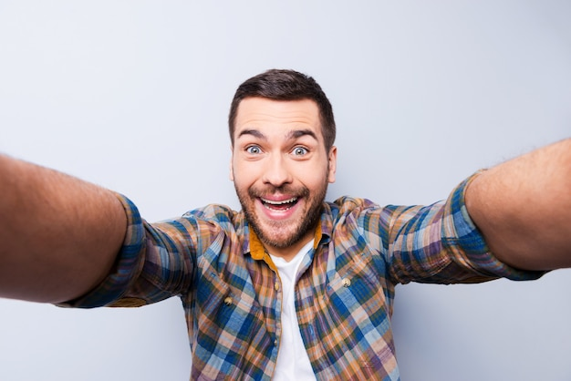 I love selfie! handsome young man in shirt holding camera and making selfie and smiling while standing against grey background