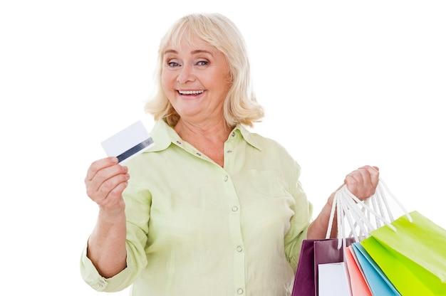 나는 쇼핑을 좋아합니다! 흰색 배경에 격리된 채 신용카드를 보여주고 쇼핑백을 들고 있는 행복한 노년 여성