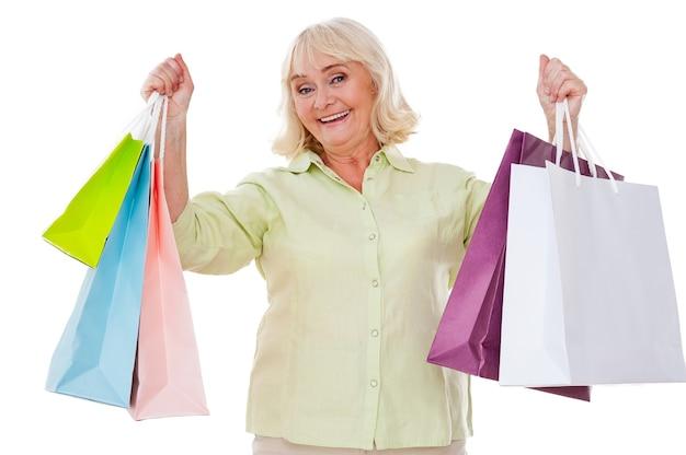 나는 쇼핑을 좋아합니다! 흰색 배경에 격리된 채 쇼핑백을 들고 손을 뻗고 웃고 있는 행복한 노년 여성