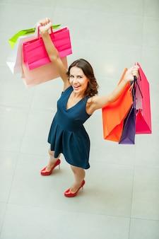 나는 쇼핑을 좋아합니다! 쇼핑백을 들고 카메라를 보며 웃고 있는 아름다운 젊은 여성의 상위 뷰
