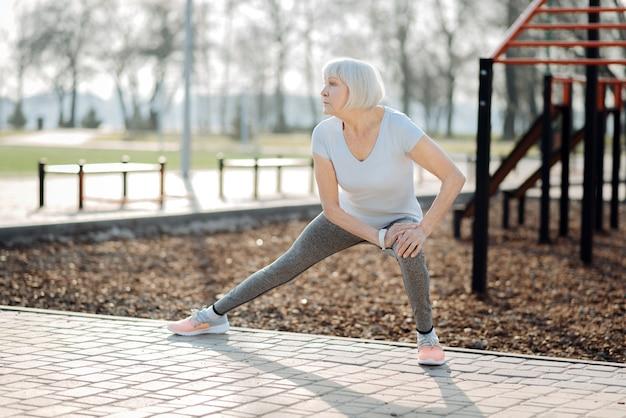 Я люблю спорт. серьезная пожилая женщина в спортивной одежде и упражнения на открытом воздухе