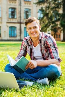 私は勉強が大好きです。本を読んで、芝生の上や大学の建物の前に座って笑っている陽気な男子学生