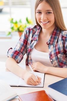 Я люблю учиться. вид сверху веселой девочки-подростка, занимающейся, сидя за столом